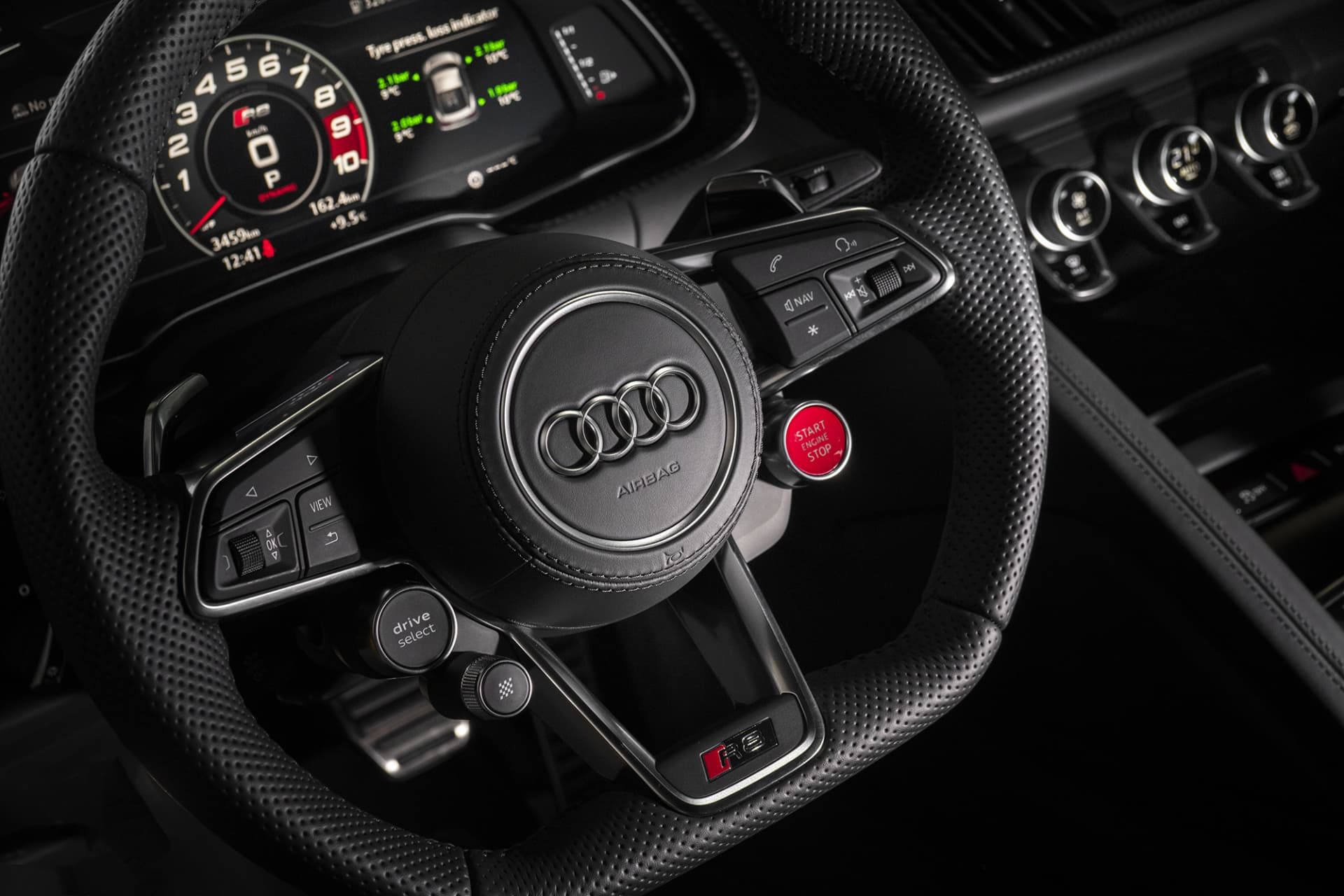 The bright red button that brings the V10 motor to life is located on the steering wheel, on the lower right hand side. The levers for the different drive modes and the Peformance ESP technology are on the left hand side.