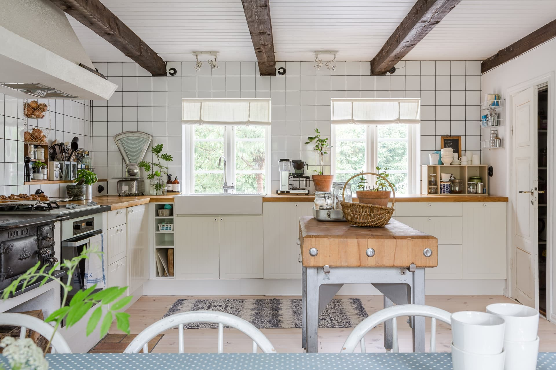 The kitchen, built at the same time as the addition, is from Ikea. The family was determined to have a wood stove in the kitchen, since they knew there had been one in the old homestead. The kitchen island is made of an old well-kept butcher's block bought at a secondhand store.