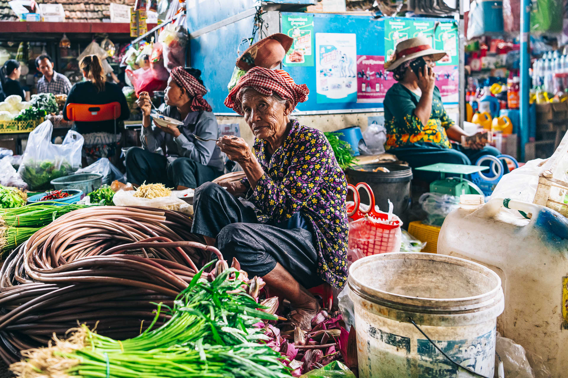 A woman enjoys her breakfast while selling fresh produce at the Kampot market.