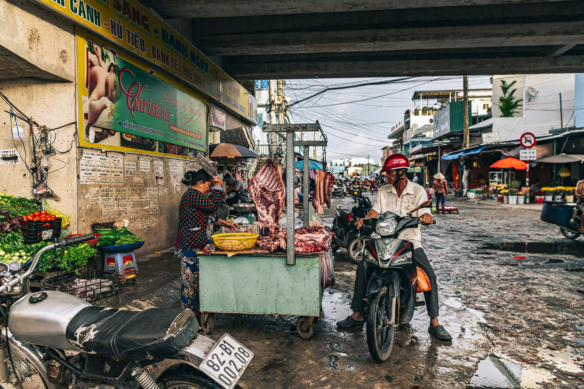 A butcher preparing a cut of meat while a customer waits on his motorbike at the Duong Dong market.