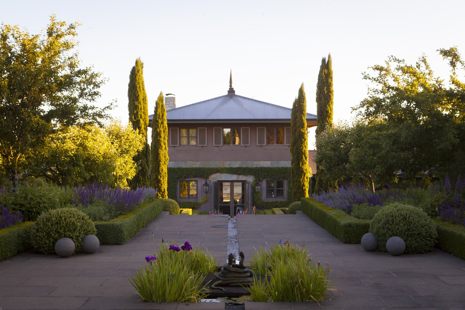 The front of the house at Stonefields shows Pauls love of symmetry and formal gardens. The water feature in the foreground is a sculpture of intertwined snakes that spout water from their mouths.