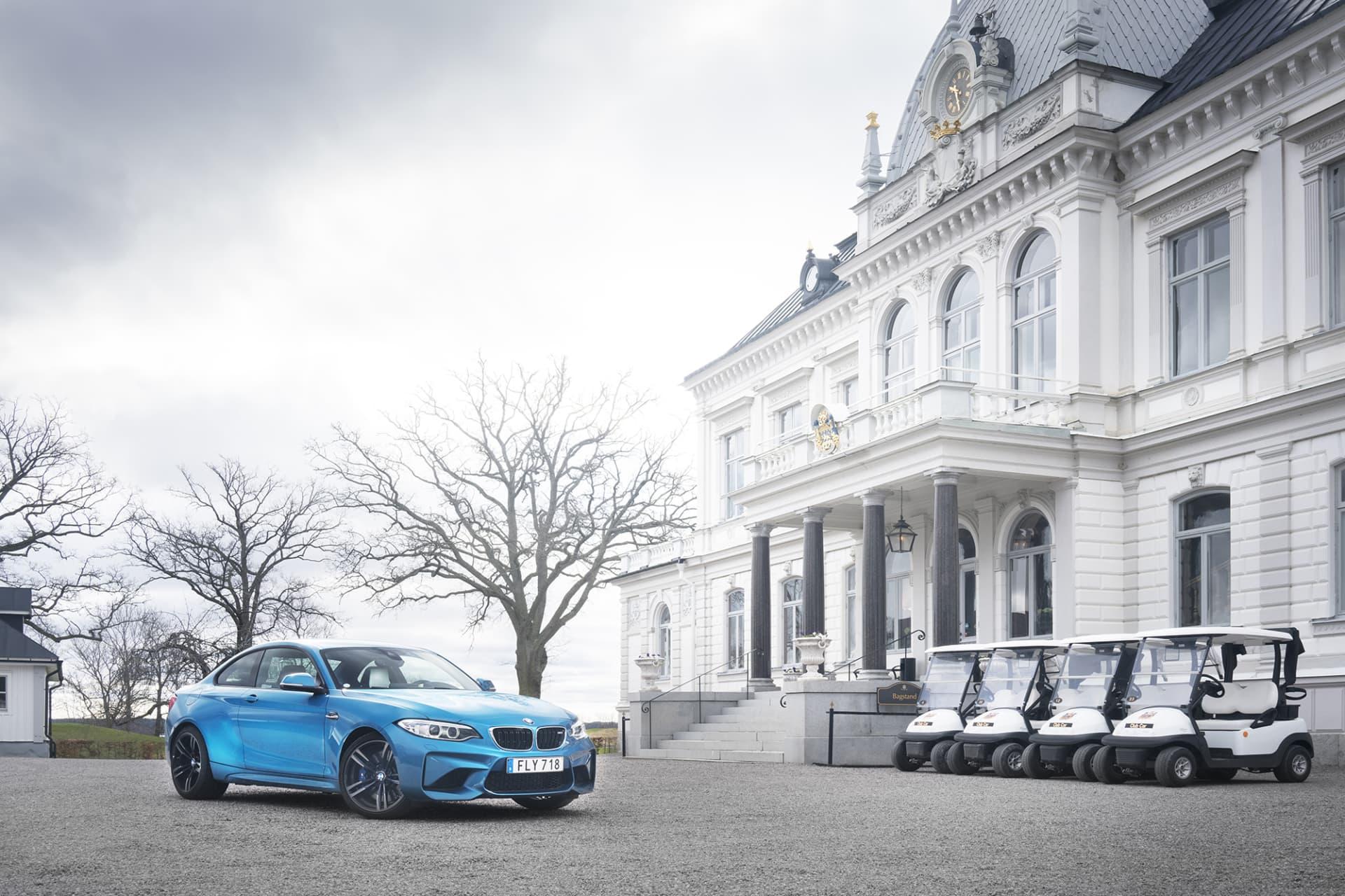 BMW M2 utanför anrika Bro Hof slott. Kombinationen av det kompakta formatet, skärmbreddare och stora luftintagen i fronten ger M2 ett riktigt coolt utseende. Färgen Long Beach-blå gör verkligen att bilen sticker ut från mängden.