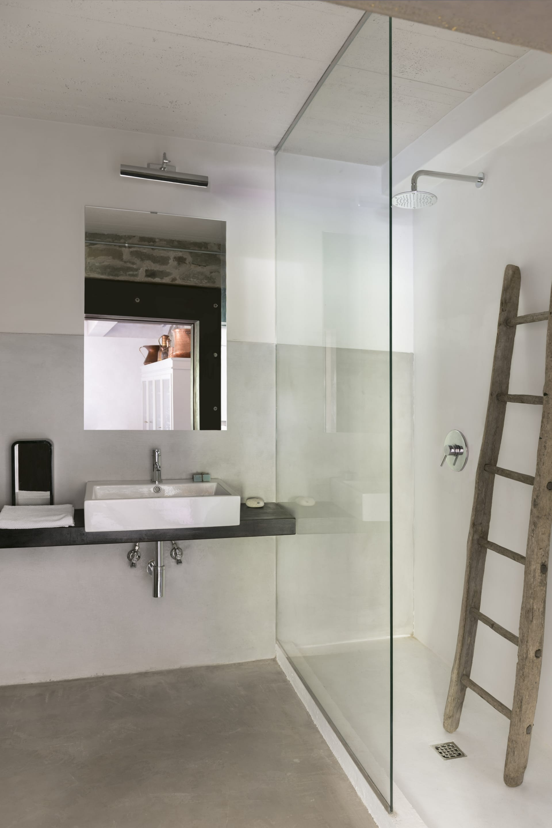 In the bathroom, concrete floor and resin walls. The old ladder serves as a towel rack, the sink rests on a large chestnut shelf.