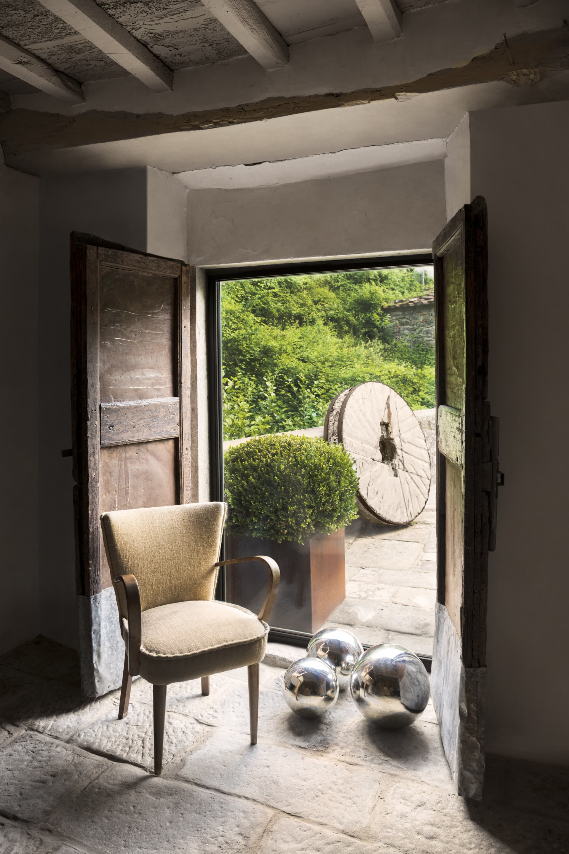 A reading room overlooking the bridge. The 50s chair has been restored by Laura. On the ground, mirrored spheres amplify the light. Outside, in addition to the boxwood vase, you can see a mill of the mill used as a decorative element.