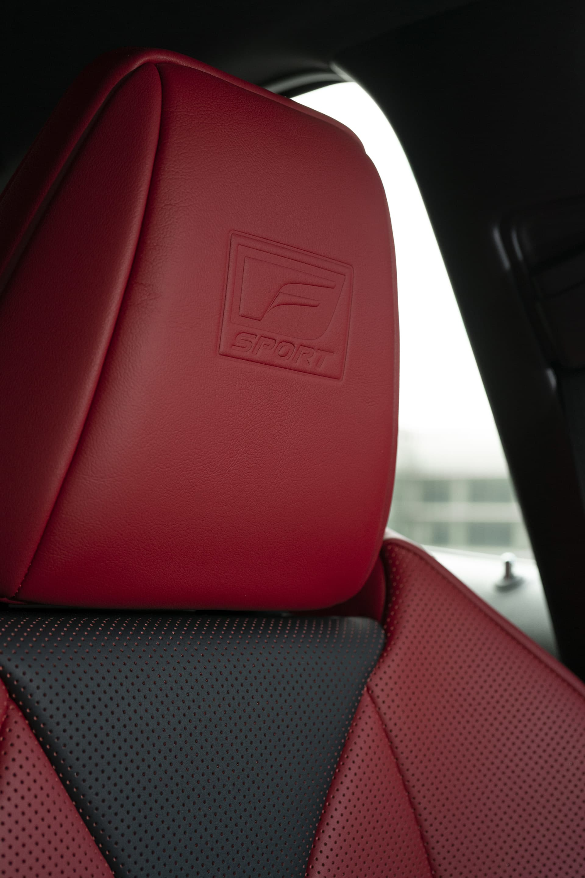 The red leather headrest embossed with the F-sport emblem.