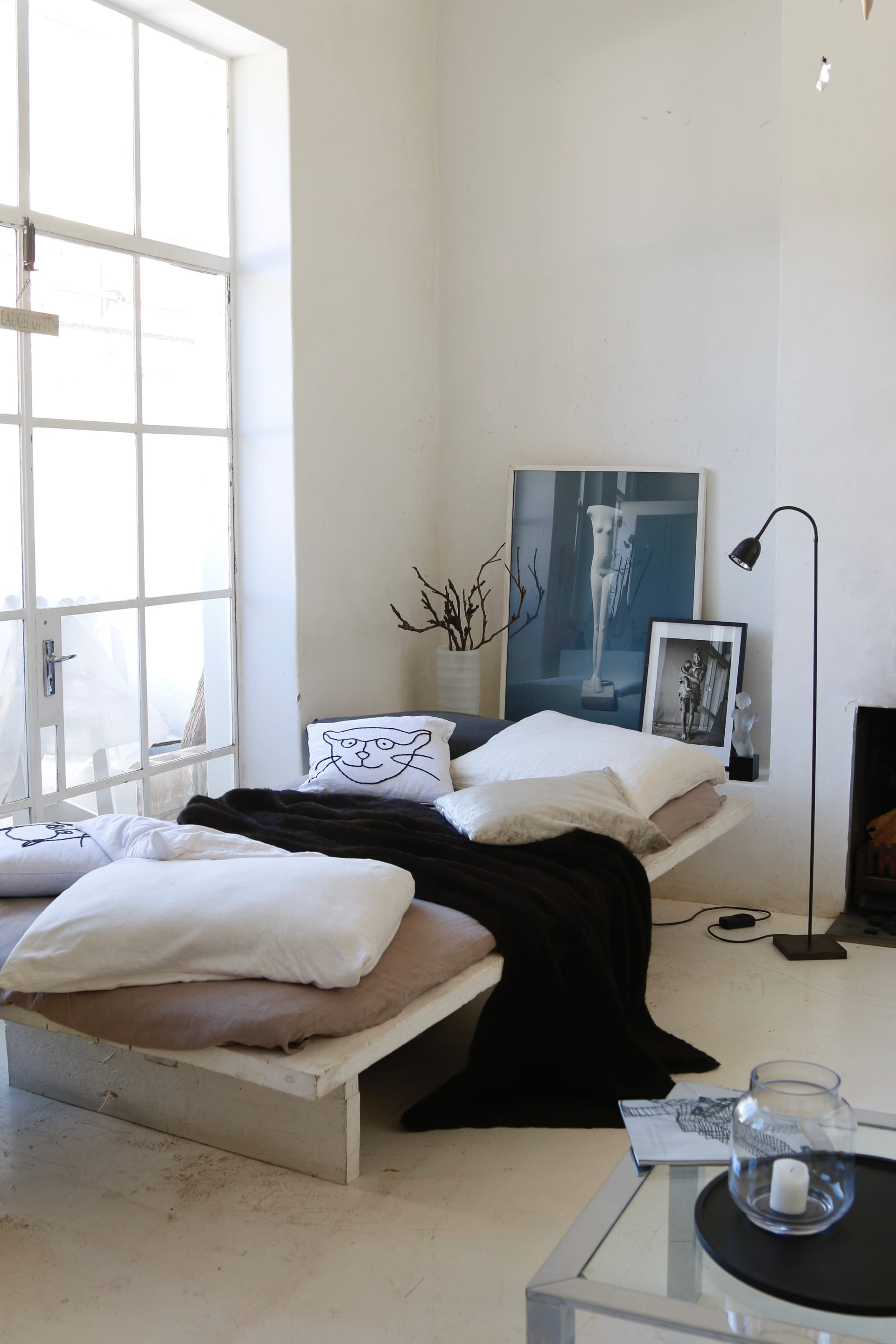 Thisall-white living space has been punctuated with a black lightning, black and white photo frames, atexturedthrow and black wooden tray.