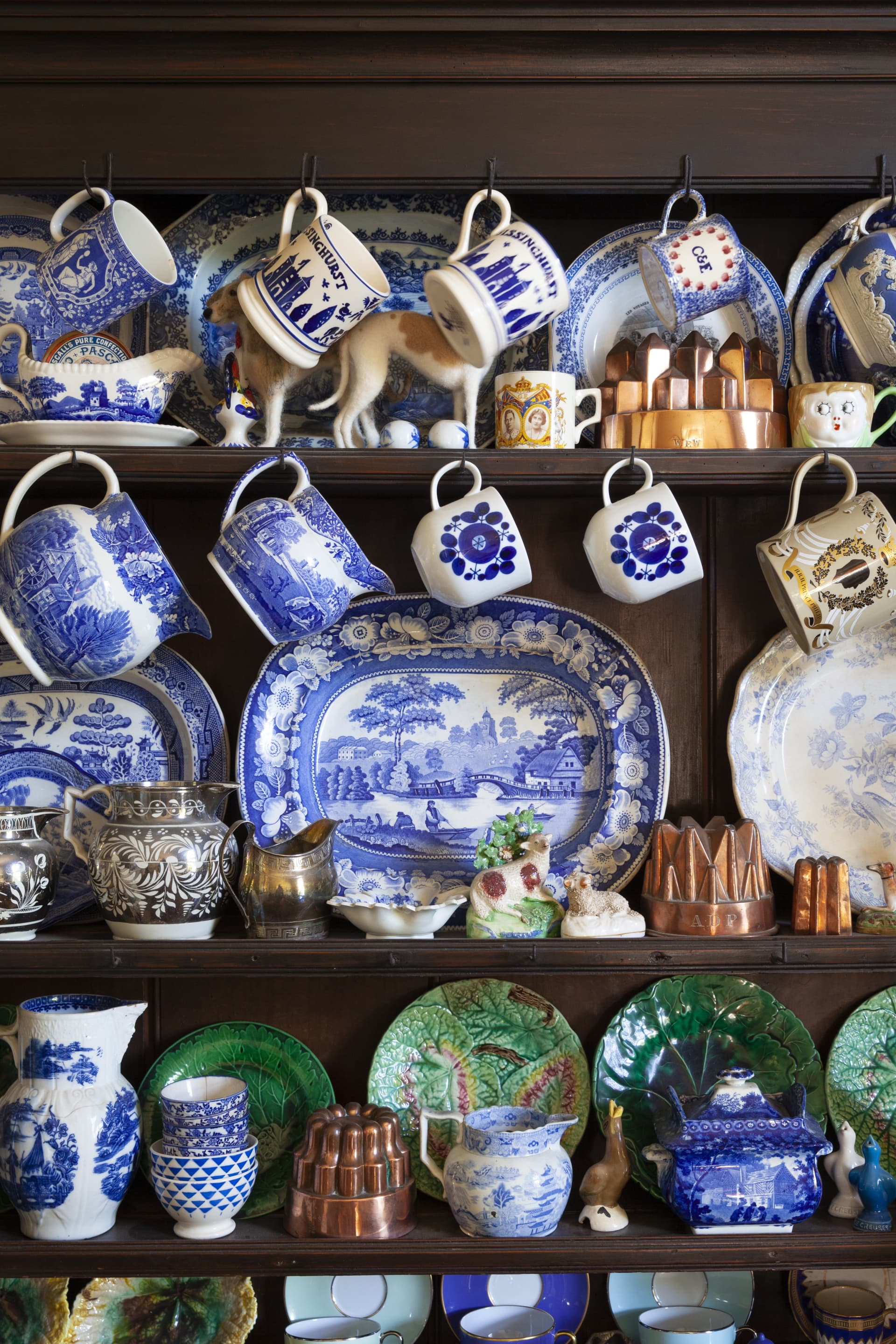 The dresser is filled to capacity, with a collection of early and modern blue and white china and majolica plates.