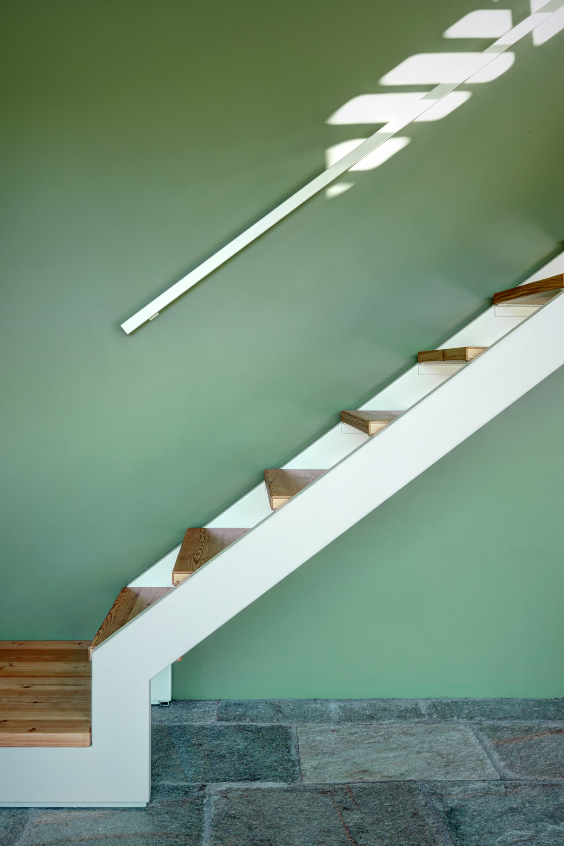 White metal and larch wood make a gentle contrast with the green painted wall.