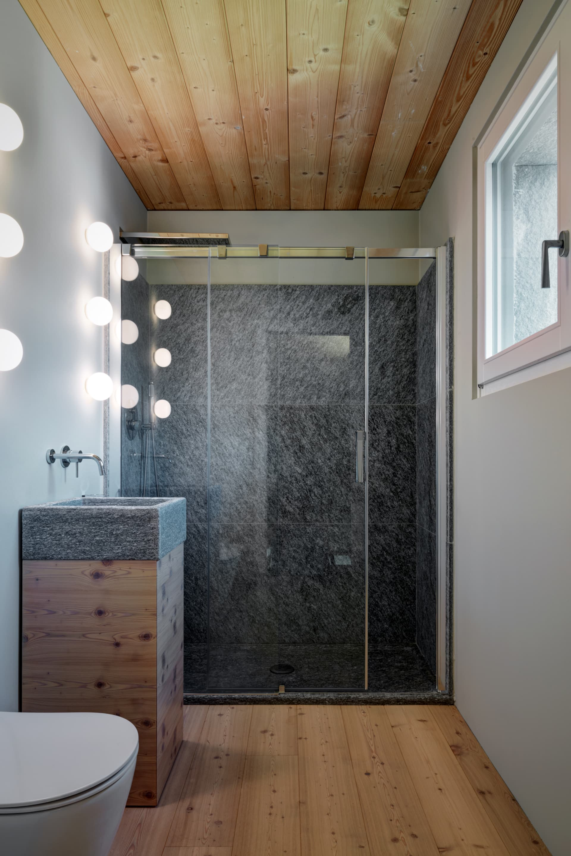 How to make the most out of a tiny room: the bathroom has it all. Look at the stone sink especially designed for the space.