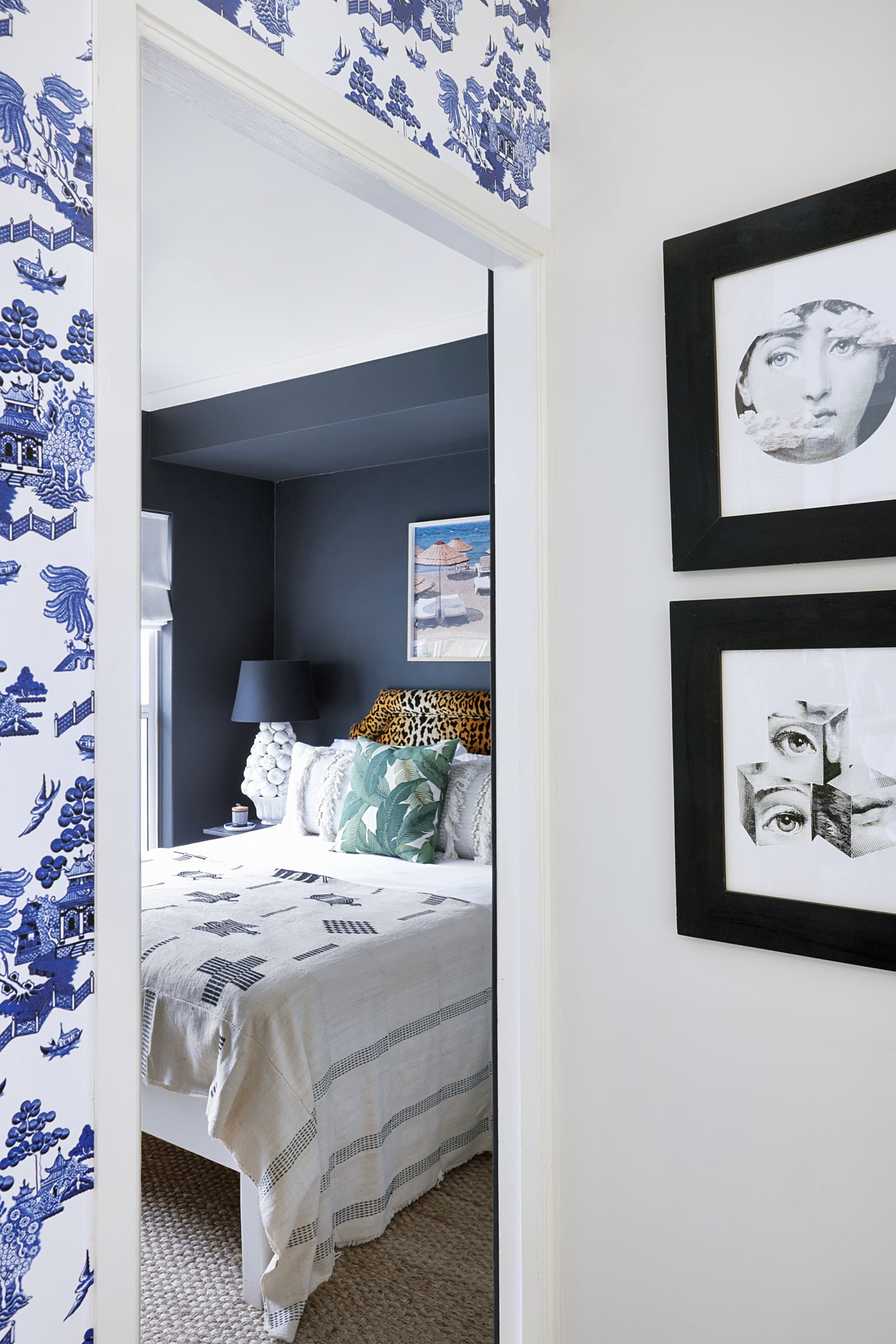 A custom wallpaper frames the bedroom door alongside Fornasetti prints. © Micky Hoyle