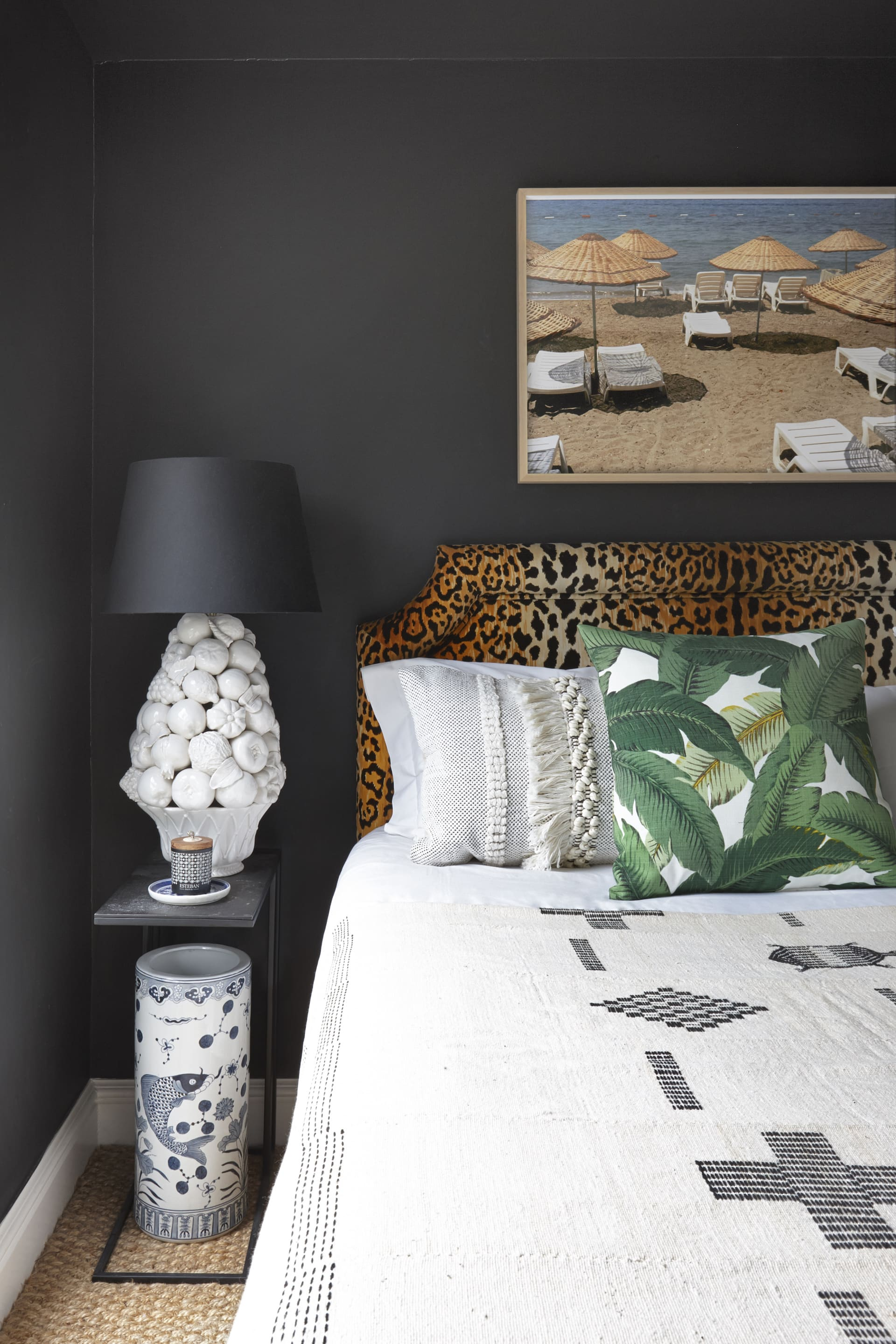 In the uniquely eclectic bedroom a framed photograph by Jen Jengo hangs on matt black walls above a leopard print headboard. © Micky Hoyle