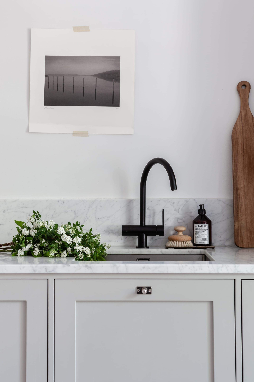 Köket har stommar från Ikea och luckor från Picky Living målade i en varmgrå kulör. Blandare från Tapwell ochposter på väggen av fotografen Kim Cramer.