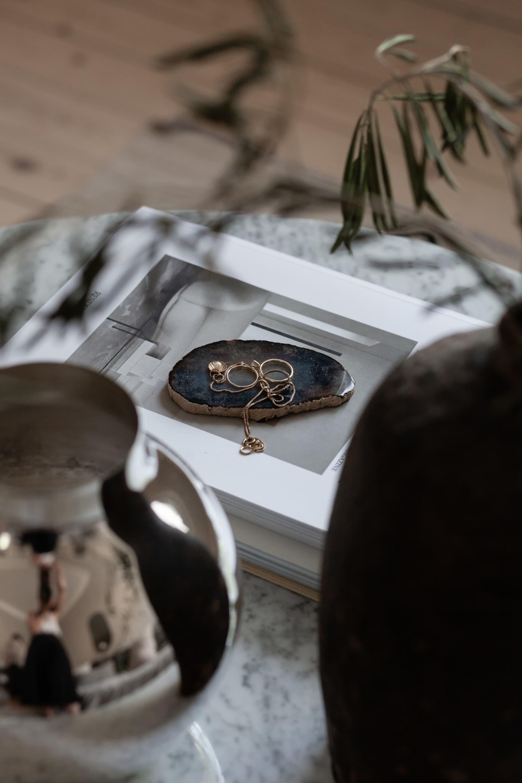 Fint blickfång! Några smycken placerade på en fin sten bildar ett stilleben i vardagsrummet.