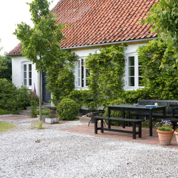 Uteplats med svarta trädgårdsmöbler på innergården, de små träden är lindar och på huset klänger blåregn.