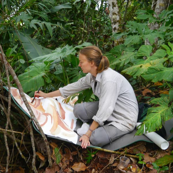 Elin painting surrounded by the nature of the Amazon.