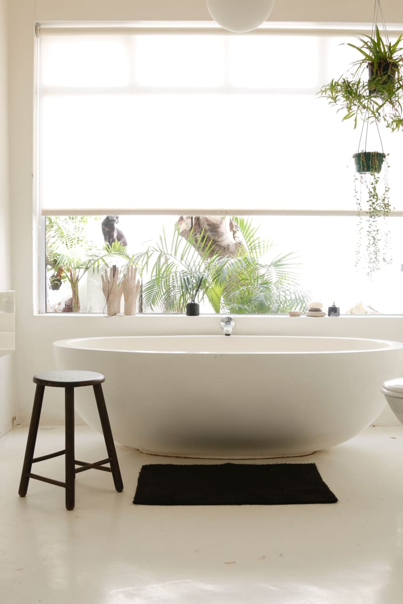 The main hero of the bathroom is this large white stone bath. The owner has introduced simple accents of black in the bathmat and towels.