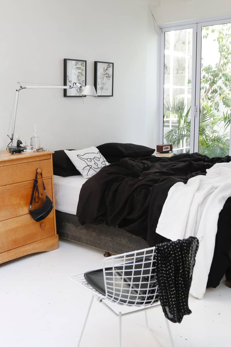 Black hemp bed linen and a simple cedarwood chest are the only contrast in this all-white bedroom which looks out onto a small leafy urban courtyard.