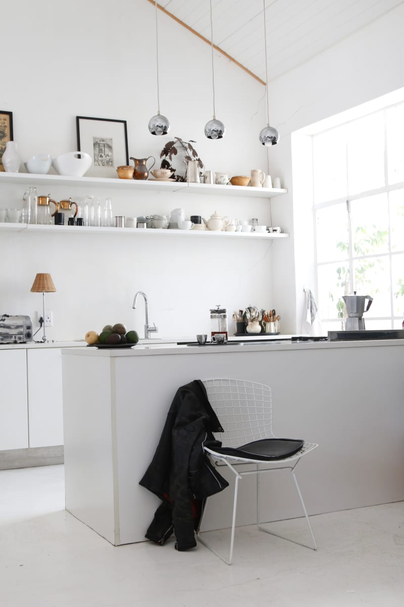The functional white kitchen is a practical space with open shelves for crockery and glassware, here again accents of black are introduced in the pictures and tableware items.