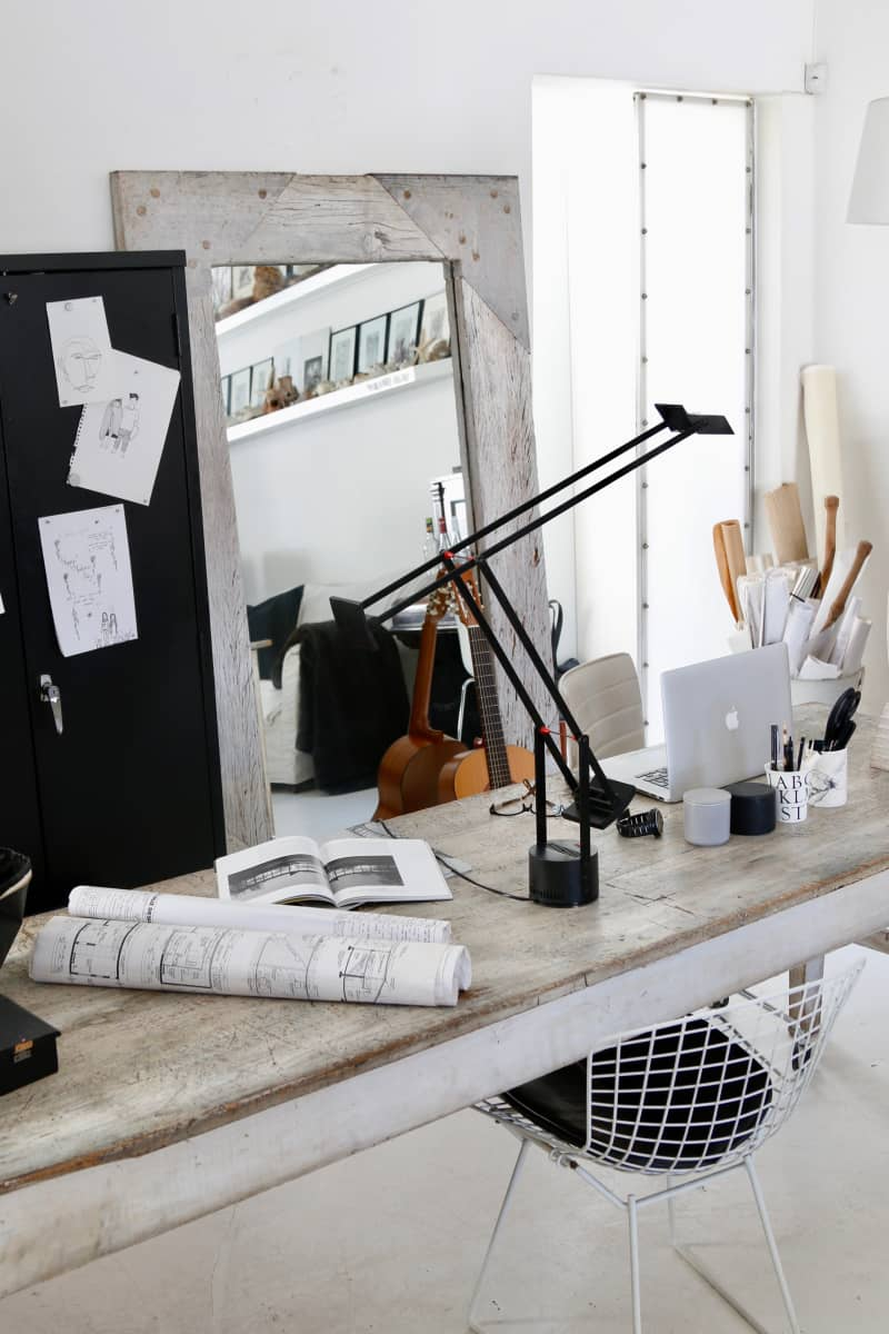 The work area is part of the main living space. It has an old workbench sourced from a country shop used as a desk, and a black metal filing cabinet for storing the owners' samples and paint colors. Her favorite lightning for working is a Tizio.