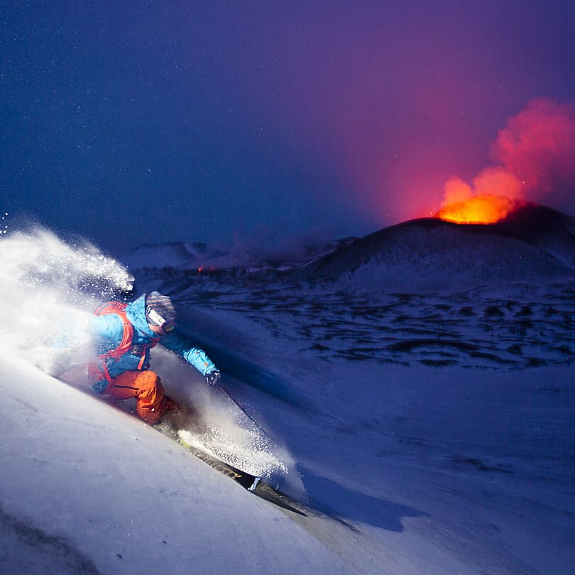 Kyla möter värme. Skidåkning med vulkanutbrott somfond.
