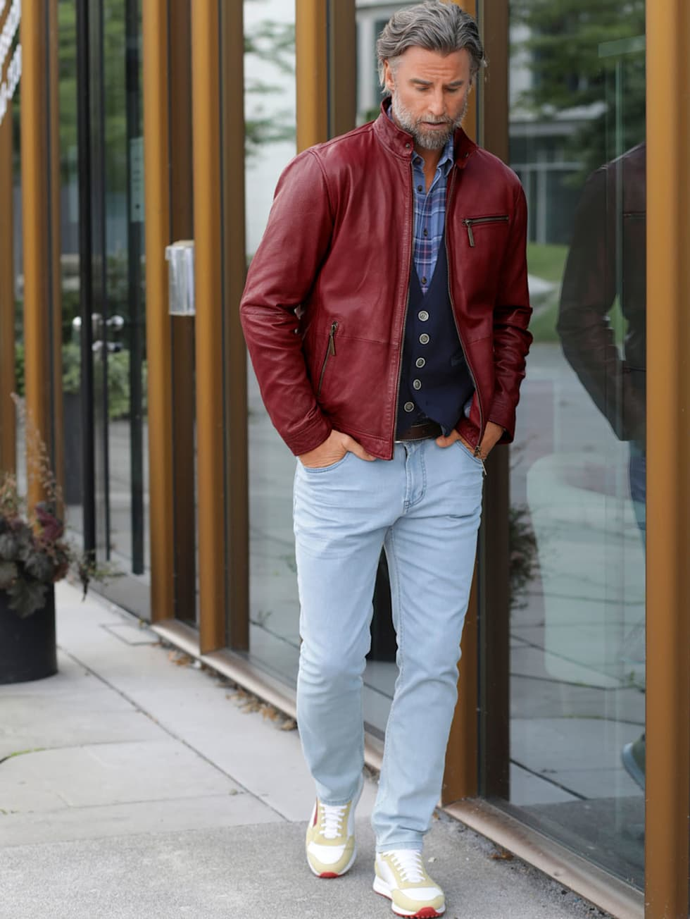 Casual-Outfit: Rote Lederjacke, blaues Hemd, dunkelblaue Weste und helle Jeans