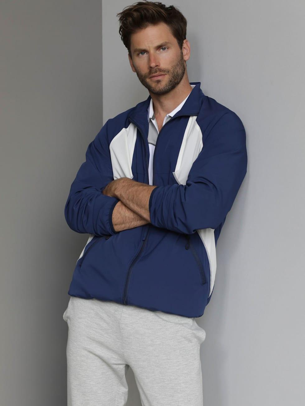 Sportivo-Outfit: Blau-weiße Trainigsjacke, graue Freizeithose und ein weißes Funktionspoloshirt