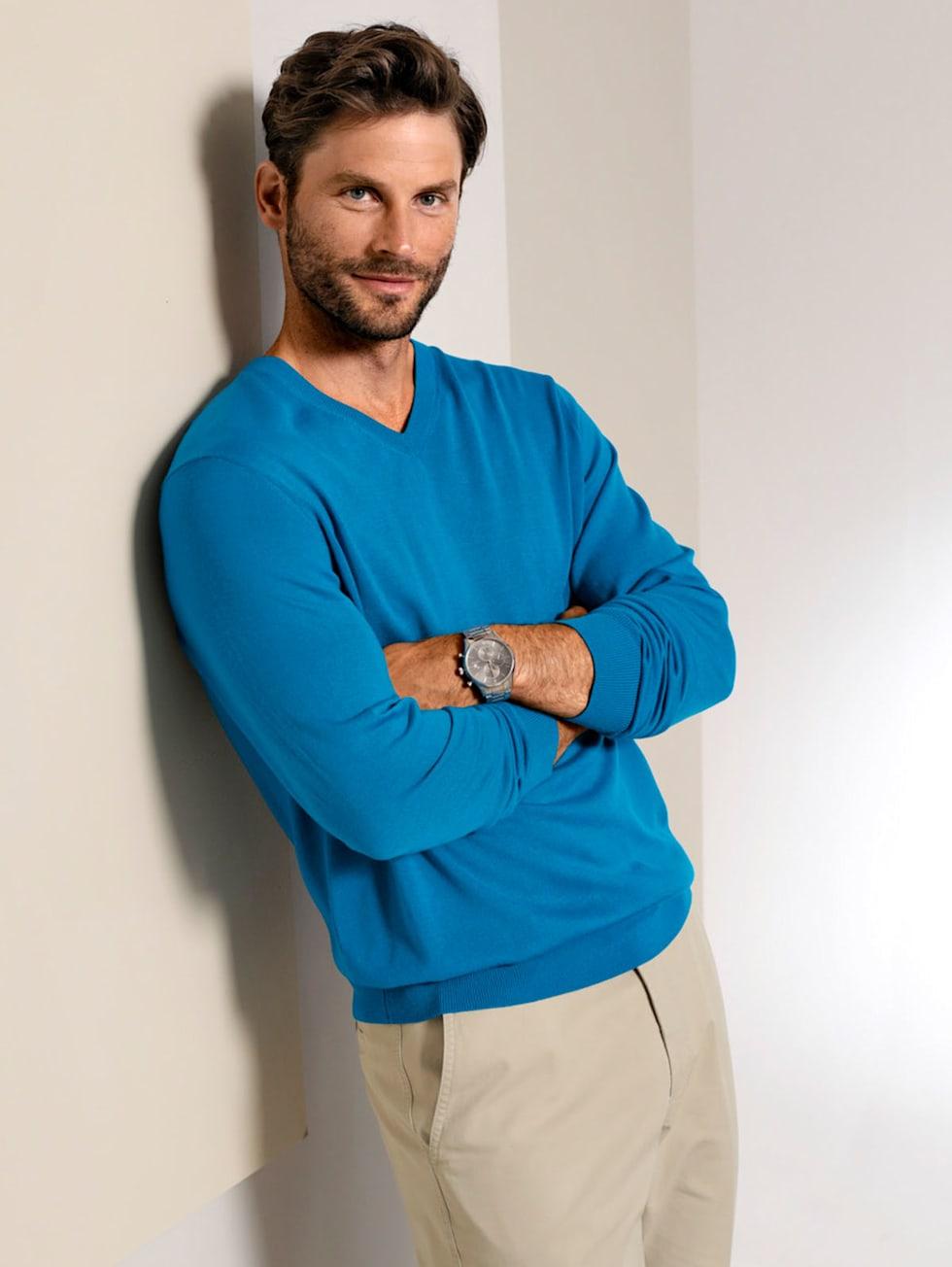 Premium-Outfit: Pullover in Türkis, Hose in Beige und eine elegante Herrenuhr