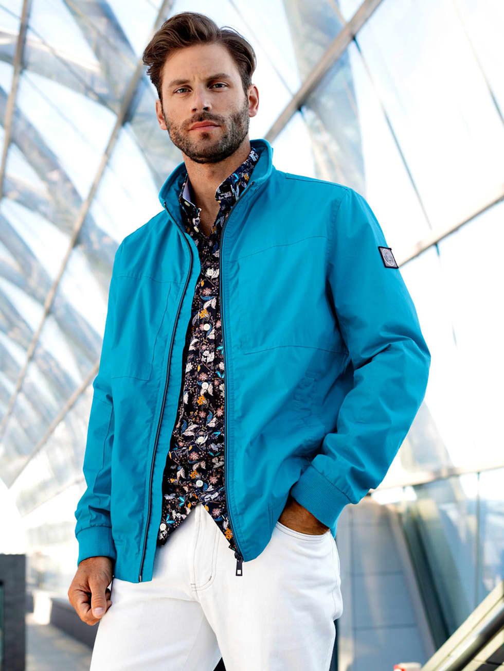Blue-Outfit: Türkisfarbener Blouson kombiniert mit Hemd in floralem Muster und einer weißen Jeans