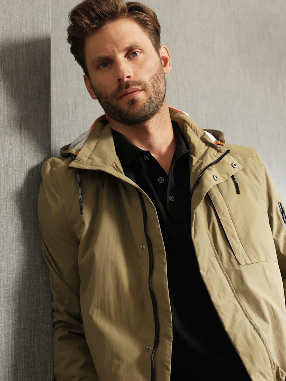 Premium-Outfit: Grüner Parka, schwarzes Poloshirt und blaue Jeans