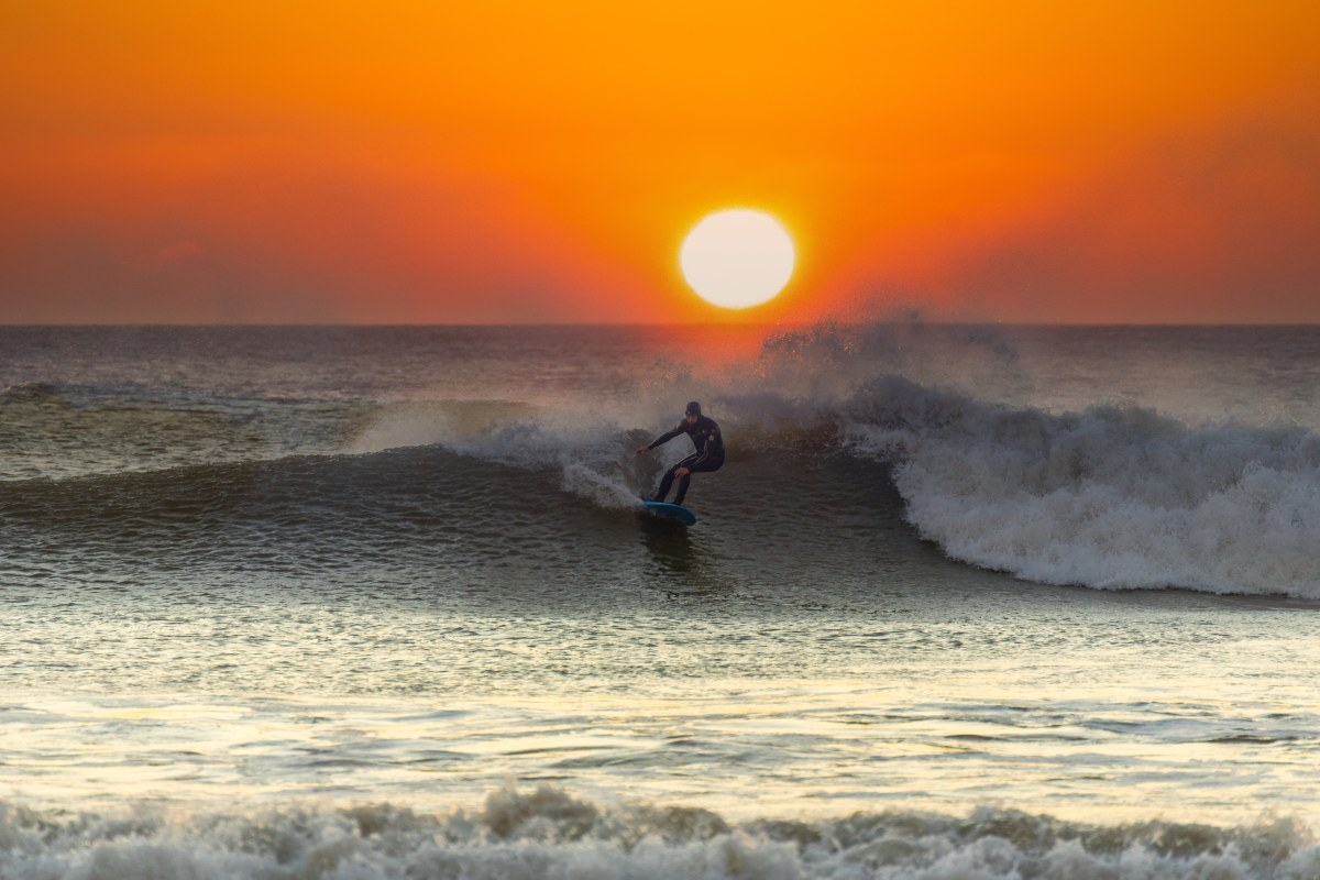 surfing as sun sets