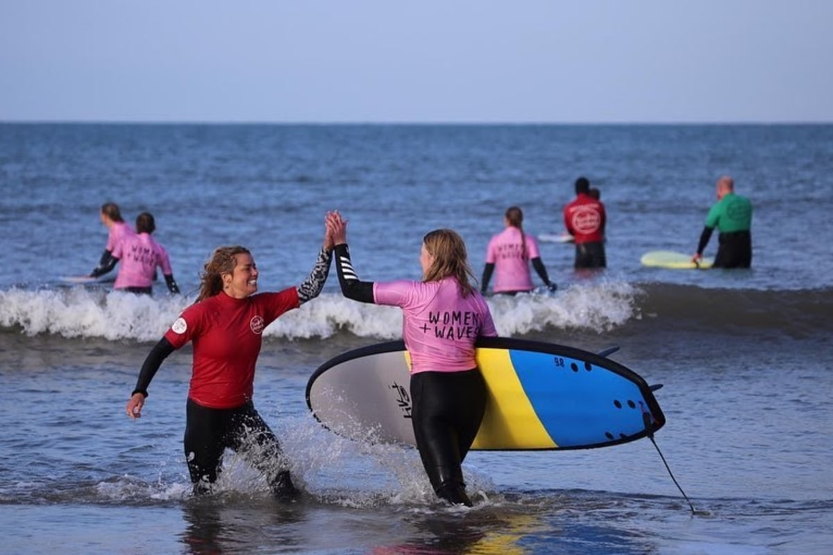 women and waves high five