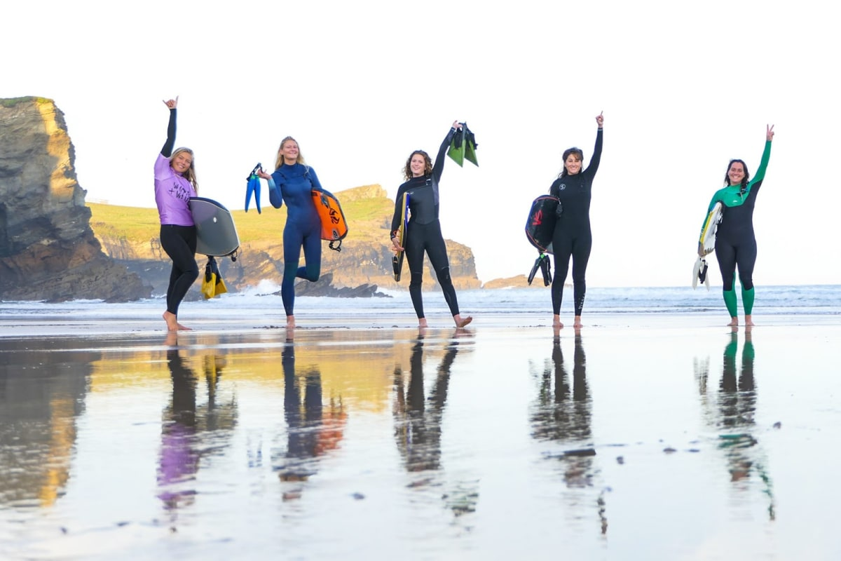 women and waves hands up on the beach