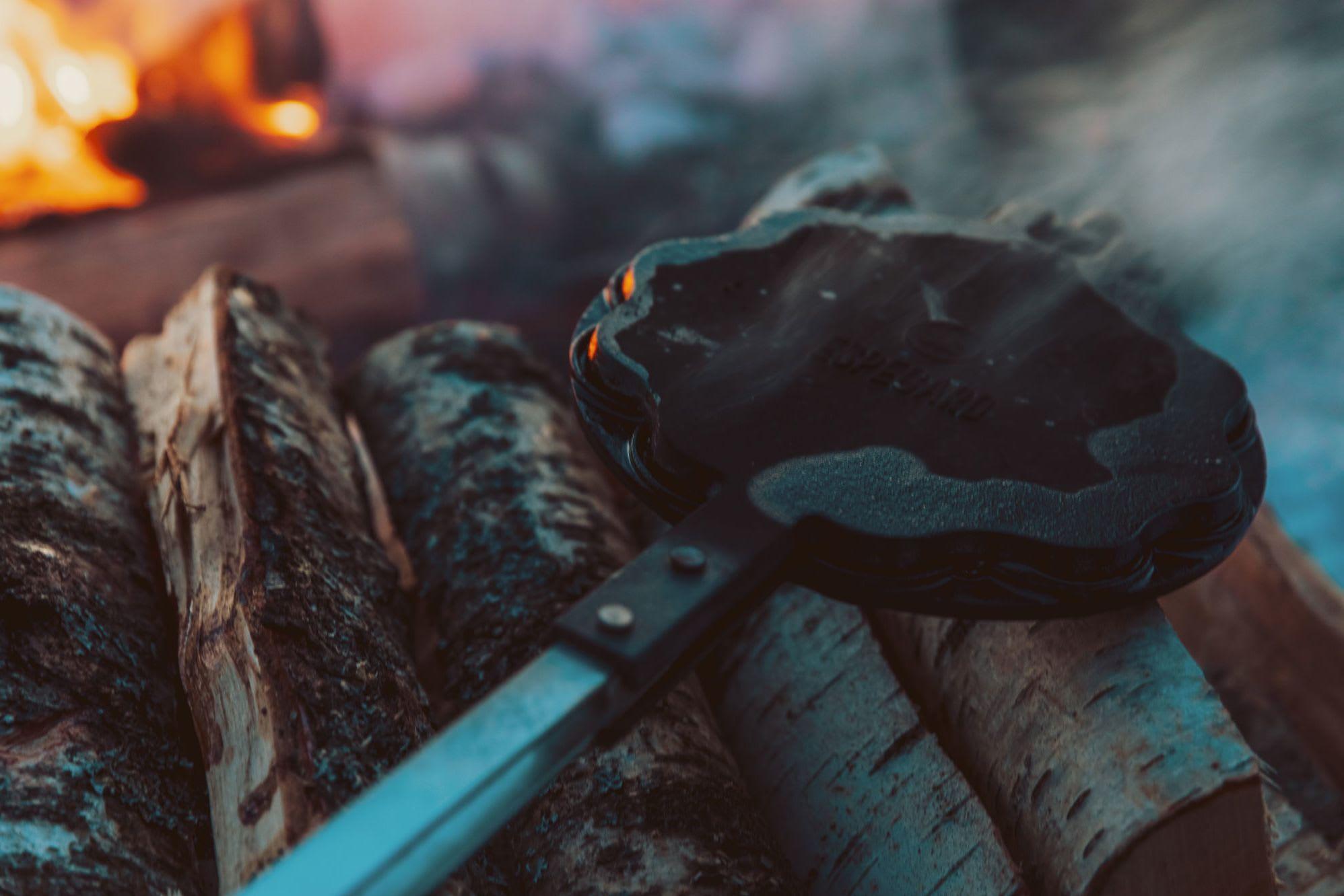 Rykende varmt vaffeljern etter å ha stått over det varme bålet.