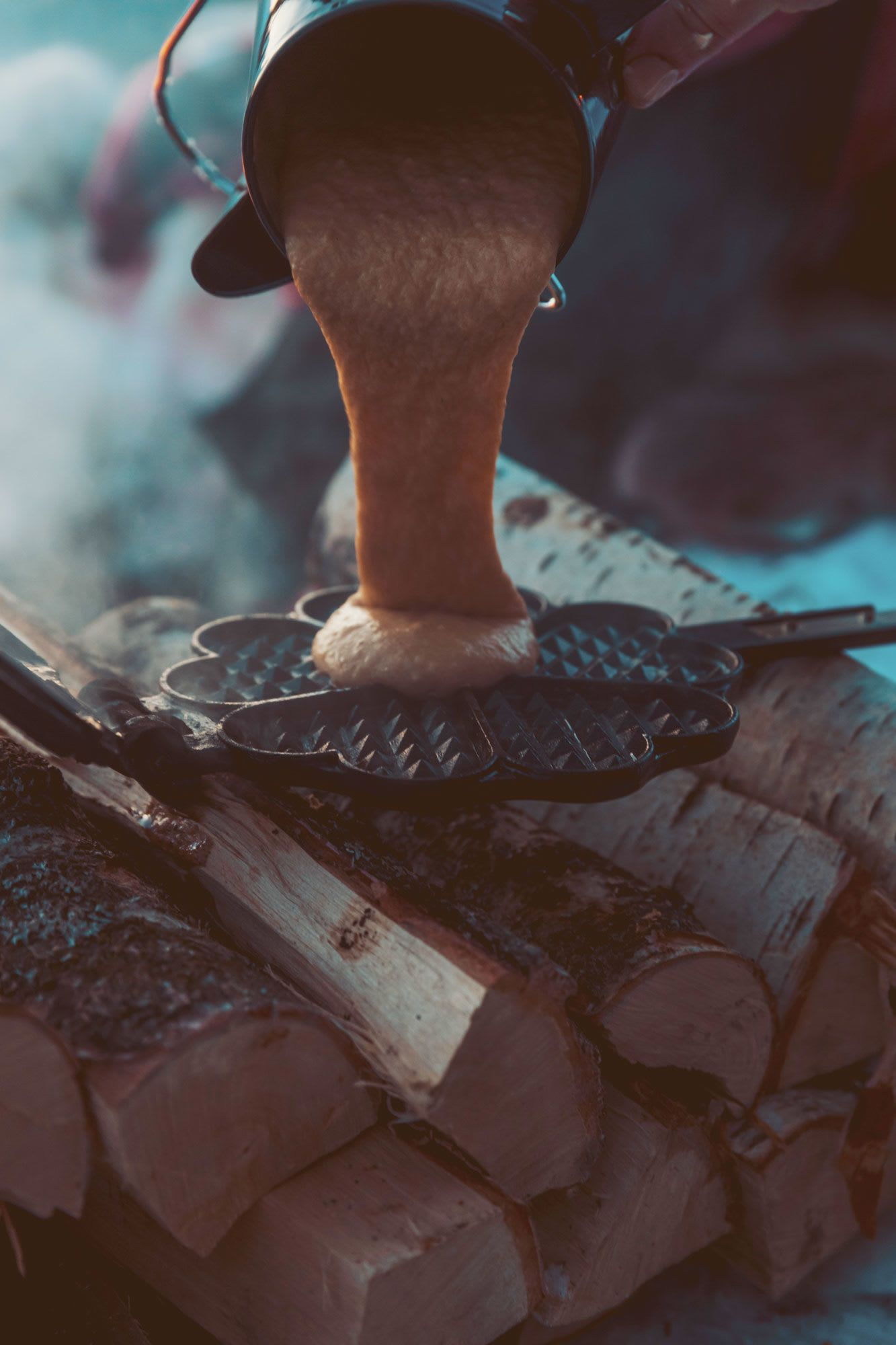 Grov vaffelrøre helles i vaffeljernet før det varmes over bålet.