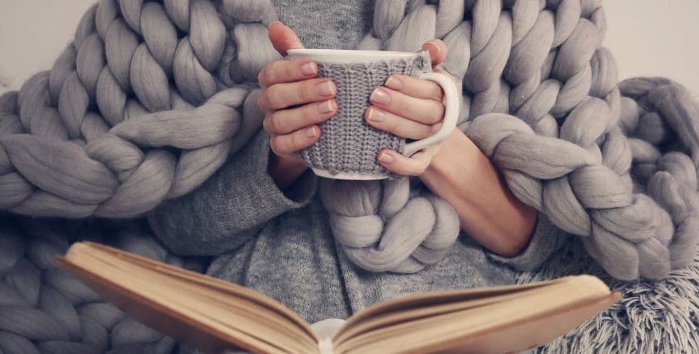 Woman holding a cup of coffee reading