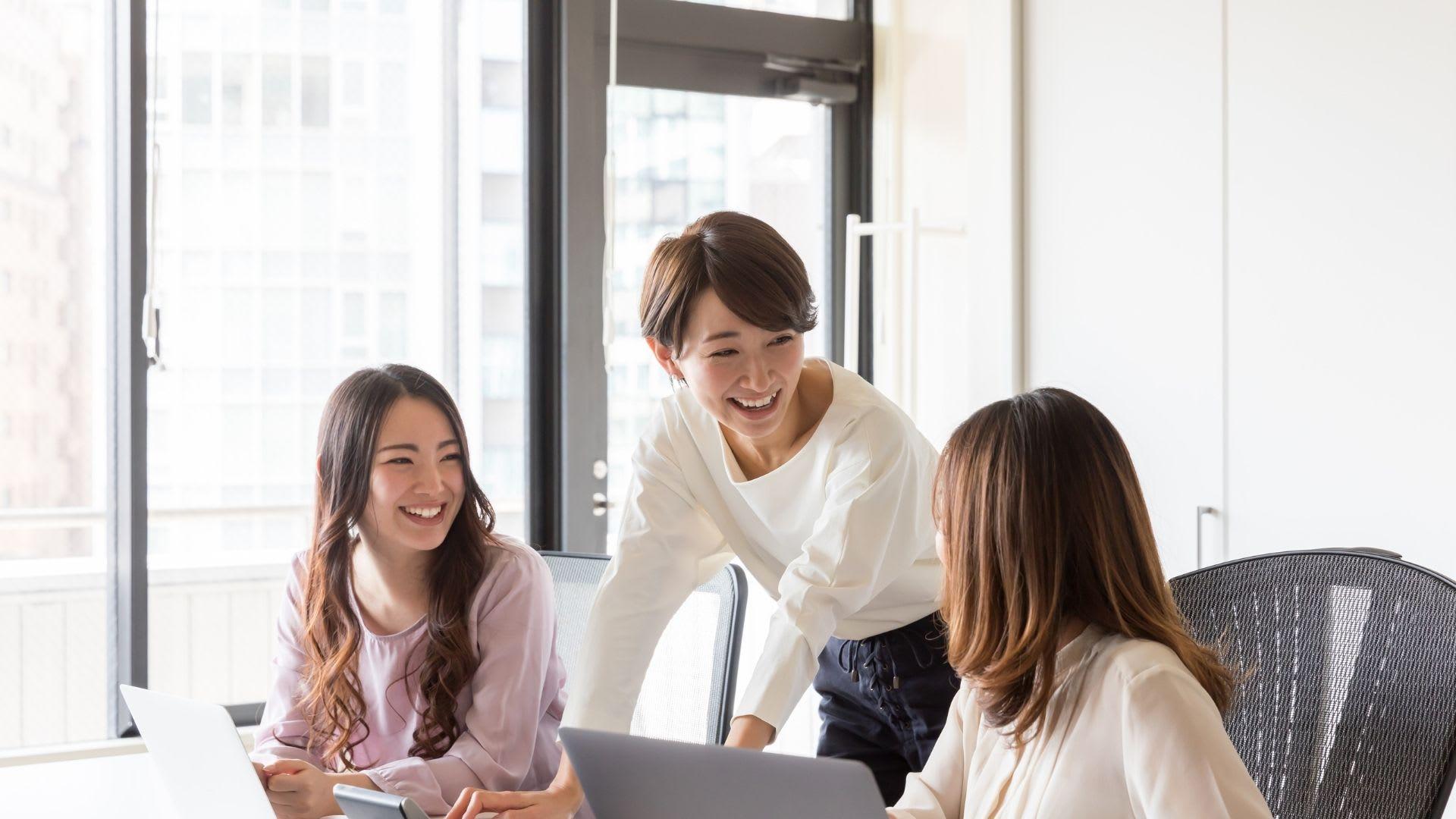 women talking by computer