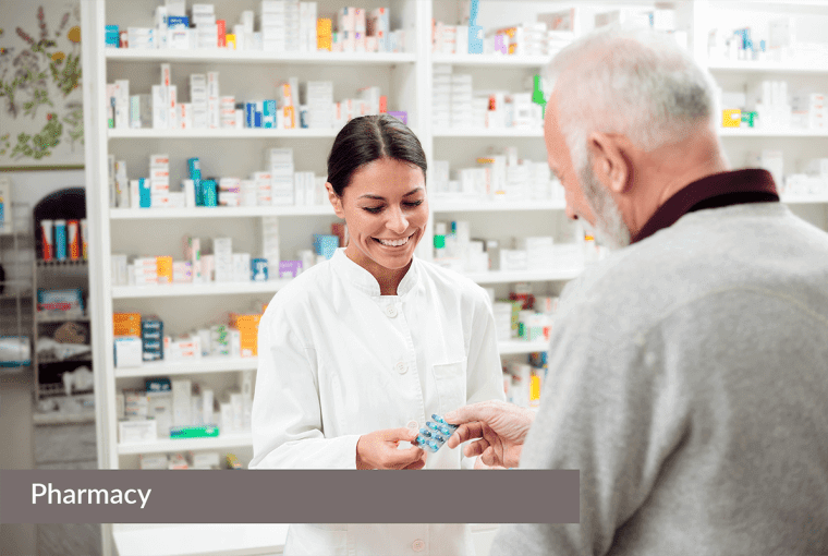 """A pharmacist giving medication to an elderly man with a label that says """"Pharmacy""""."""