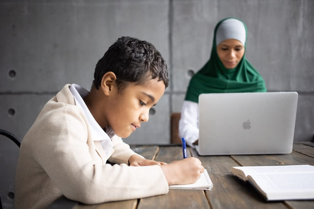 Parent working on laptop while child is working on schoolwork