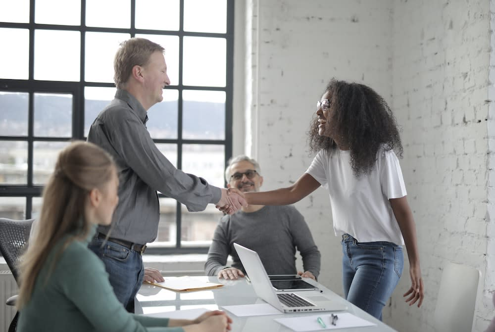 People in casual office shaking hands