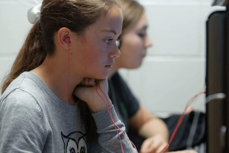 Two girls in class using headphones to listen to their desktop computers.