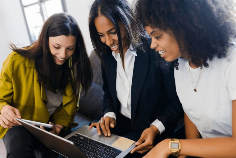 Three business women smiling at a laptop together.