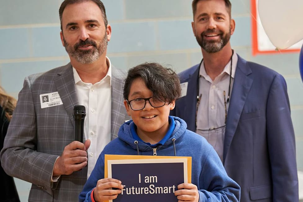 """A boy holding up a sign that says """"I am FutureSmart""""."""