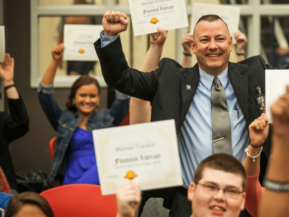 A classroom holding up financial literacy certificates over their heads.