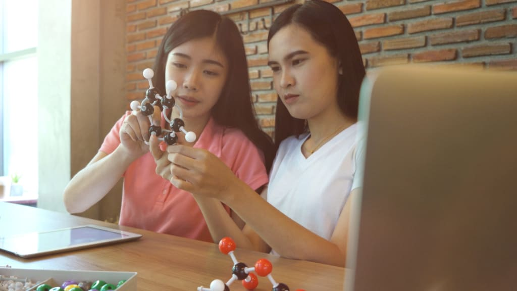 Two girls learning on chemistry subject