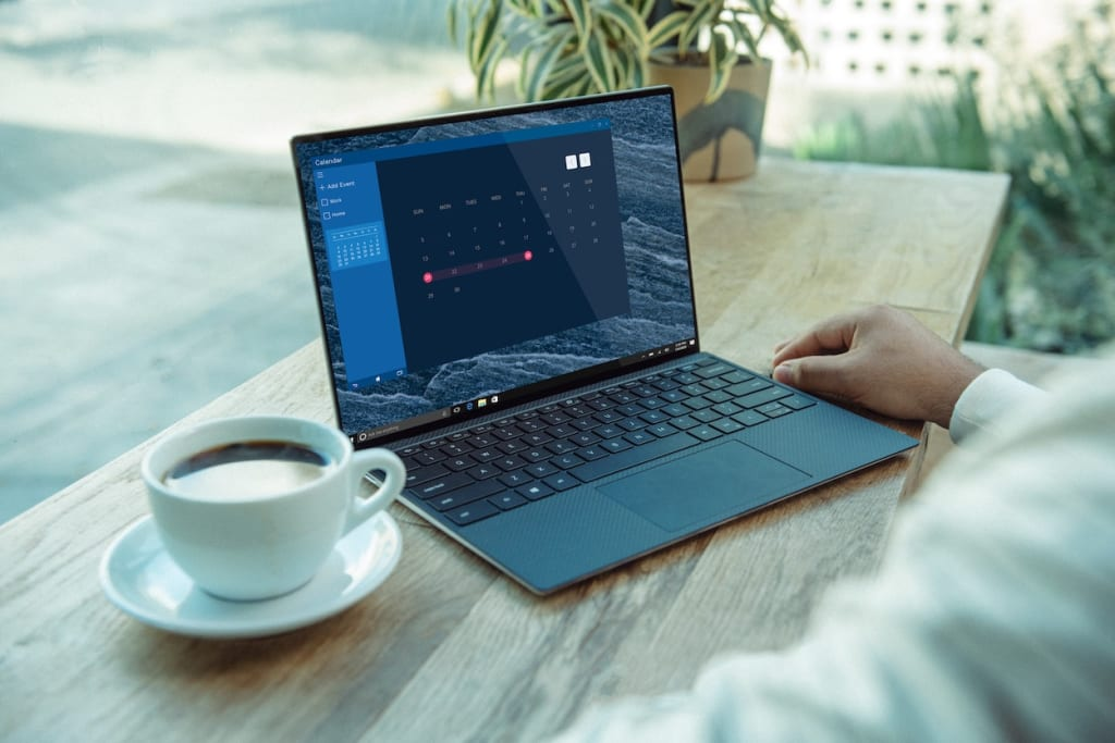 Laptop on desk with coffee mug
