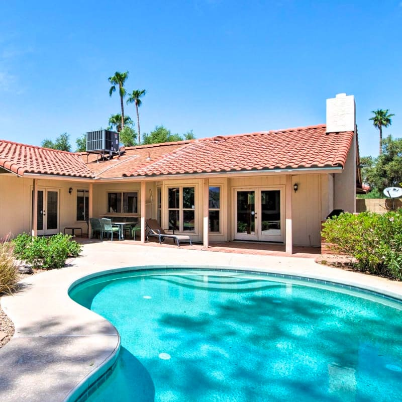 Vacation rental home in Scottsdale, Arizona with a pool and palm trees in the background