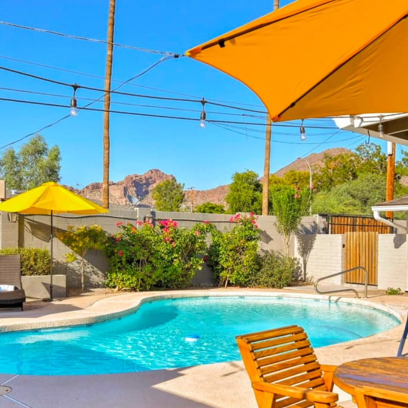 Vacation rental home in Scottsdale, Arizona with a pool, umbrellas, and mountain views