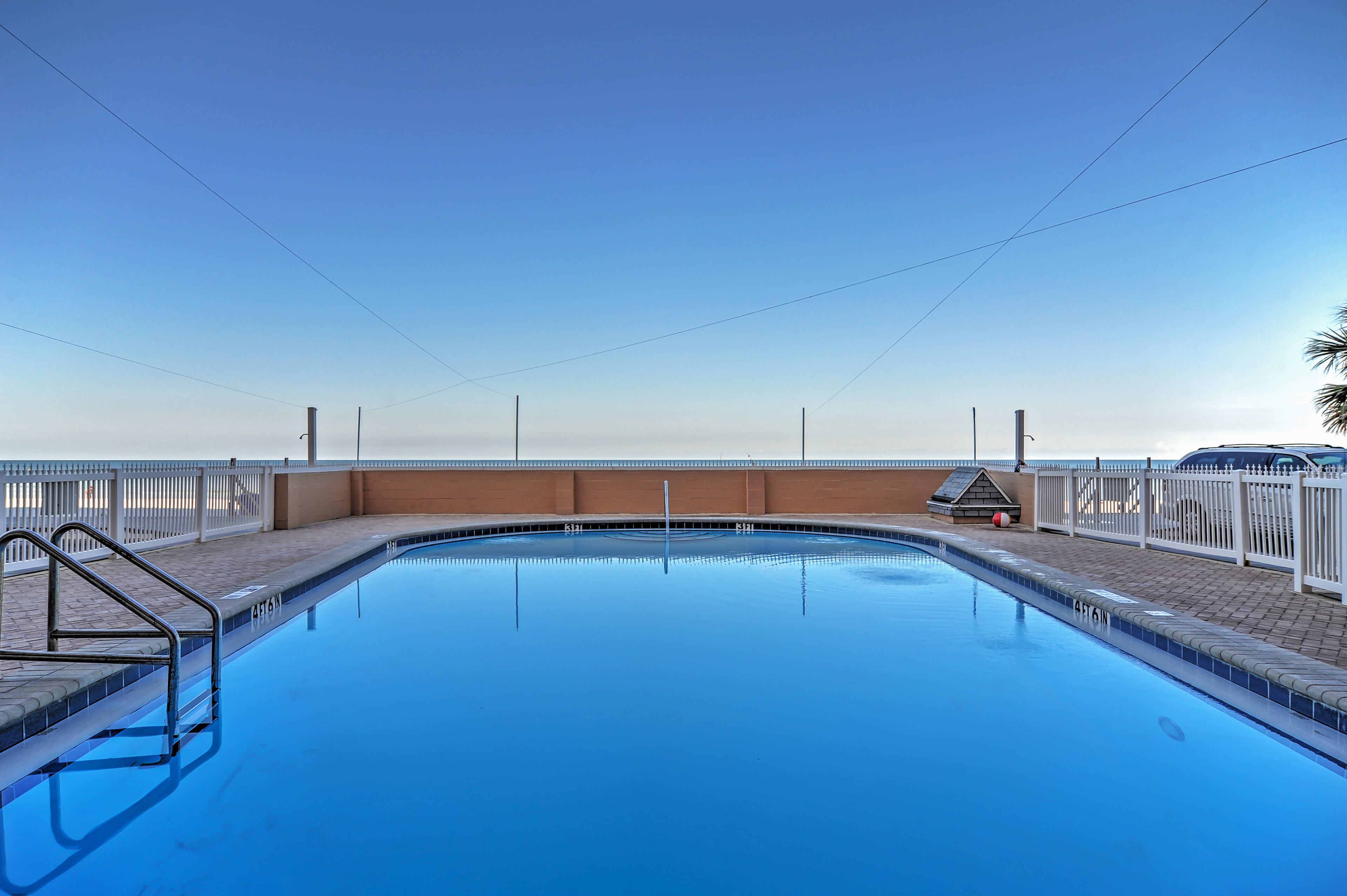 The shared swimming pool is only steps from the beach