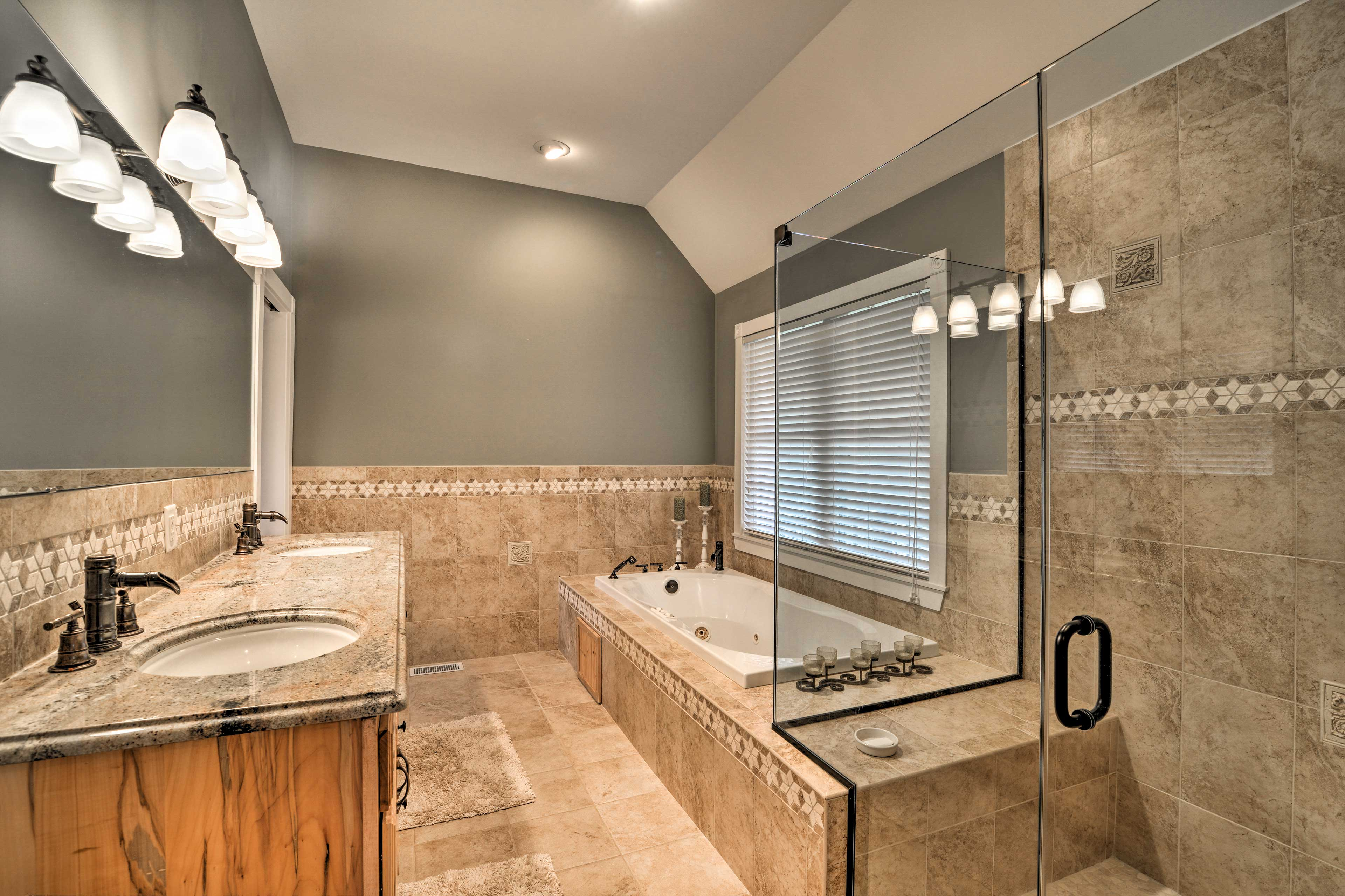 The master bathroom hosts dual sinks, a walk-in shower. and jetted tub.