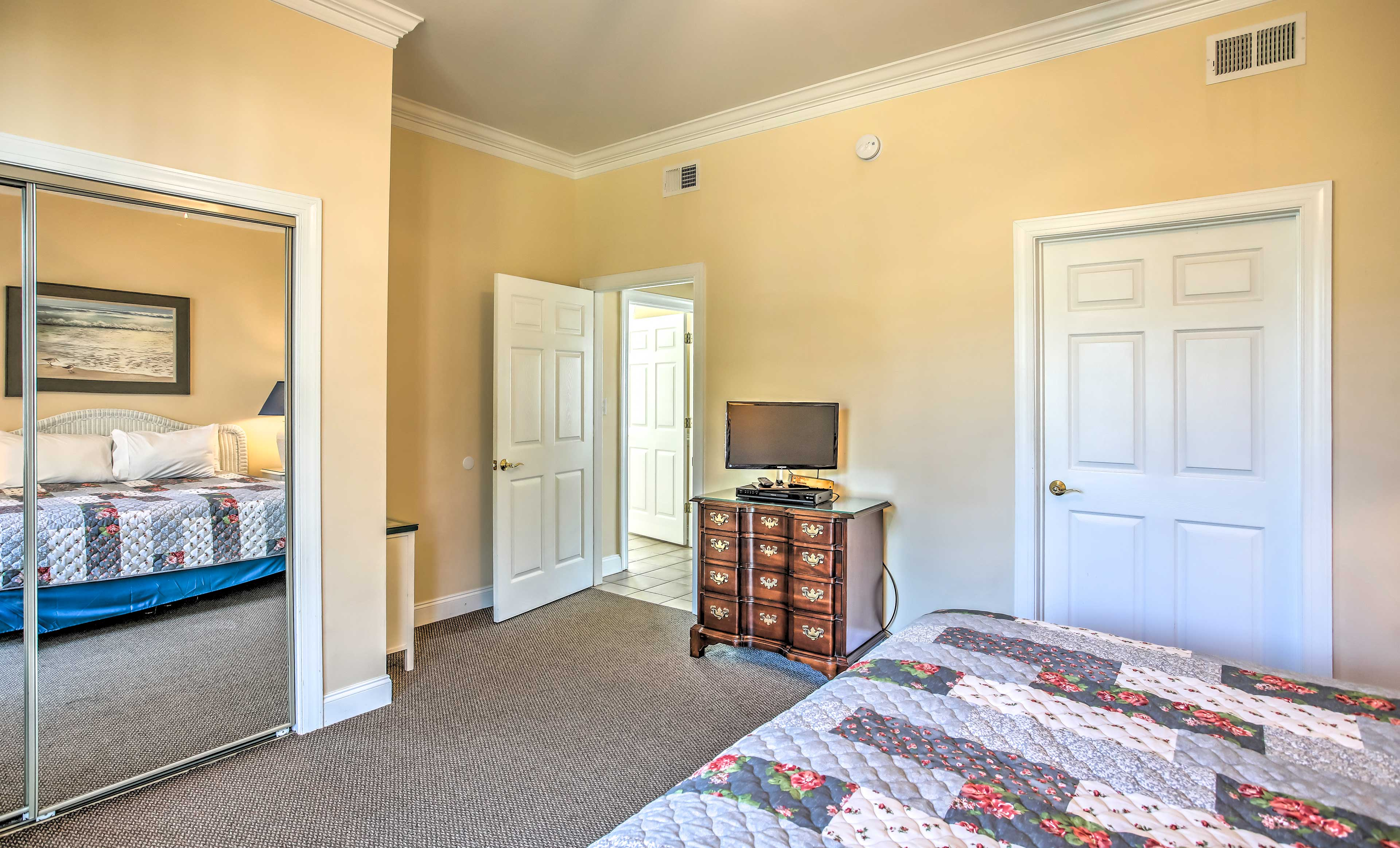 The master bedroom offers a TV and access to the patio.
